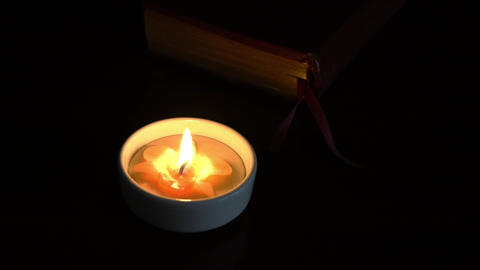 Candlelight with a bible or thick book at the background. Meditation or peace concept Live Action