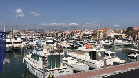 Cambrils, Spain, A boat is docked next to a body of water Live Action