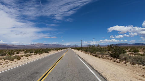 Driving down the endless desert road. Adventure travel in a desert Live Action