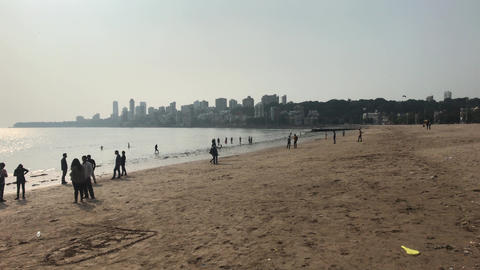 Mumbai, India - November 10, 2019: Marine Drive tourists walk on the beach part Live Action