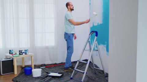 Handyman painting wall Live Action