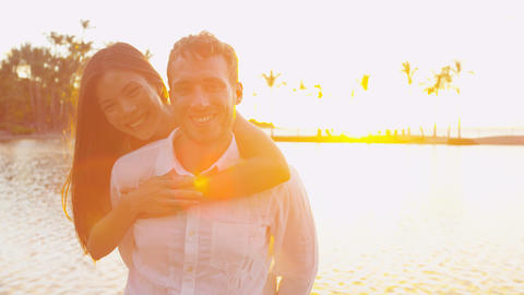 Couple portrait romantic at sunset happy in love embracing looking at camera Live Action