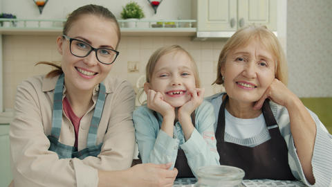 Portrait of joyful family grandmother, mother and daughter smiling in modern Live Action