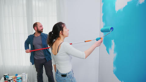 Husband and wife painting wall Live Action