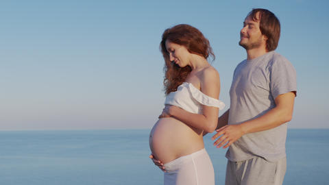 Happy pregnant couple. Husband embracing wife gently holding her belly outdoor Live Action