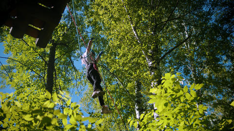 A woman crossing the rope bridge - an entertainment attraction in the forest Live Action