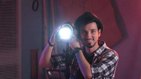 Male filmmaker adjusting professional light stand in studio, with lighting on Live Action