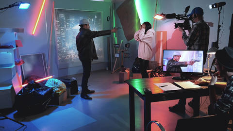 Backstage of thriller film shooting: black man trying to shoot young black woman Live Action