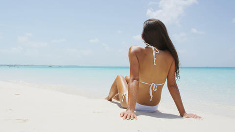 Beach vacation woman relaxing on sand happy in enjoyment under the sun Live Action