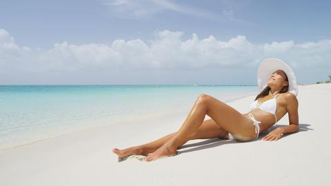 Beautiful carefree Asian American girl enjoying her beach lifestyle sunbathing Live Action