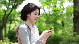Young woman taking selfie on a bench in the park 이미지