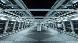 Time lapse night view of futuristic pedestrian passageway with people walking in Footage