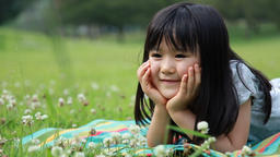 Japanese young girl relaxing on a blanket in a park, Tokyo, Japan Footage