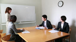 Japanese business people having a meeting at a wooden desk near a white board 이미지