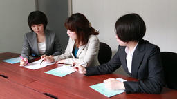 Japanese businesswomen having a meeting at a wooden desk in a modern meeting roo GIF