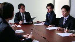 Japanese business people having a meeting around a wooden desk in a modern meeti Footage