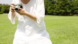 Young Japanese woman shooting with vintage camera in a park Footage