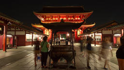 Time-lapse front view of people walking by incense cauldron at Senso-ji temple,  Footage