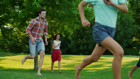 Cheerful family running in green meadow. Kids and parents playing in field Live Action