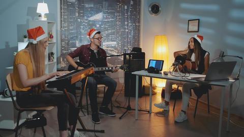 Joyful musical band in Santa hats singing Christmas song and playing instruments Live Action