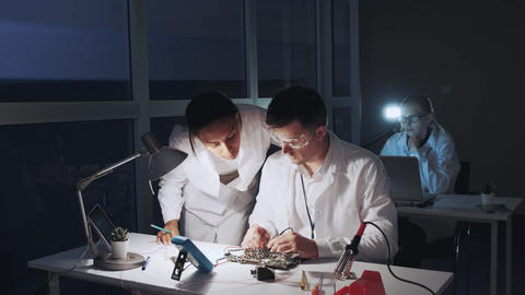 Mixed race electronics engineers in white coats working on motherboard using Live Action