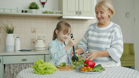 Little girl cooking salad mixing vegetables in bowl and chatting to cheerful Live Action