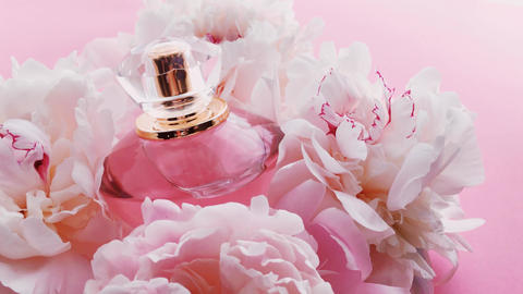 Pink perfume bottle with peony flowers, chic fragrance scent as luxury cosmetic Live Action