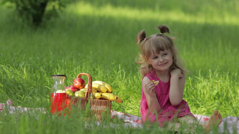 Weekend at picnic. Caucasian child girl on grass meadow with basket full of Live Action
