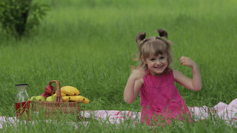 Weekend at picnic. Lovely caucasian child girl on green grass meadow sit on Live Action