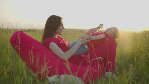 Playful mom tickling laughing baby girl outdoors Live Action