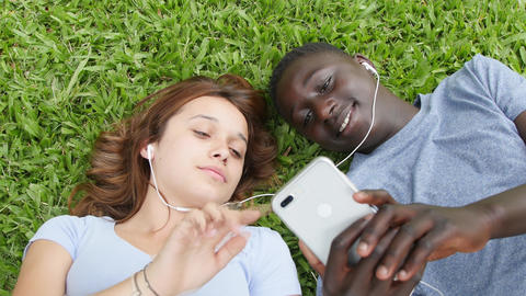Multi ethnic couple of teenagers seated on a park hearing music. Slow motion Live Action