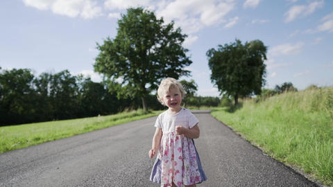 Baby girl walking on country road Live Action