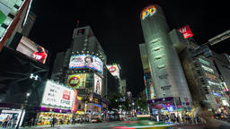 Time lapse footage of pedestrians and vehicles passing near Shibuya 109 at night Footage