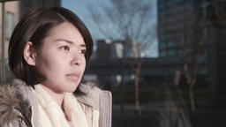 Slow-motion shot of young Japanese girl looking away with a serious look in an o Footage