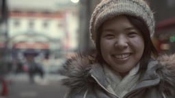 Slow-motion shot of young Japanese girl smiling at camera in small alley in Toky Footage