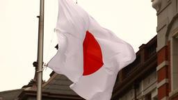 Japanese flag fluttering in the wind near Tokyo station, Tokyo, Japan Footage