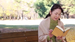 Japanese mature female reading a book on a bench in a city park in Autumn Footage