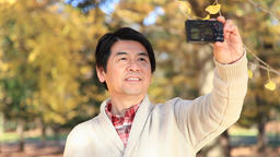 Japanese mature male taking selfies in a city park in Autumn Footage
