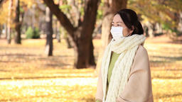 Japanese mature female wearing a mask feeling sick in a city park in Autumn Footage