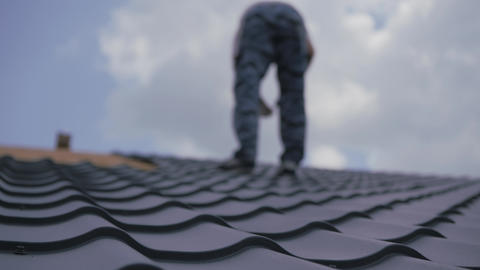 Roofing works. The installer screws the metal tile to the roof crate. Roof Live Action
