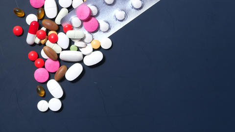 colorful pills spilling on dark background top down Live Action