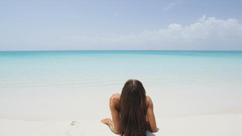 Vacation beach travel holidays - woman enjoying sunbathing looking at ocean Live Action