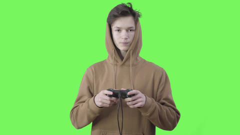 Addicted Caucasian teenager gaming at chromakey background. Portrait of absorbed Live Action