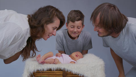 Mother father and son kiss a newborn girl. Replenishment in the family. Family Live Action