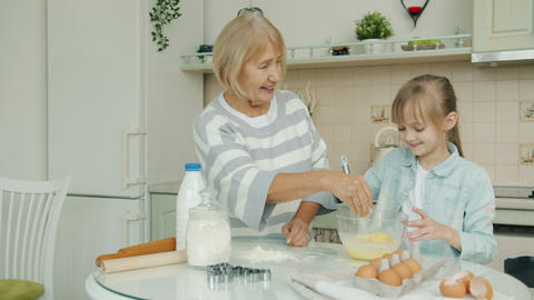 Happy child and granny cooking food mixing ingredients making dough at home in Live Action