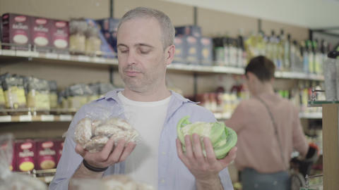 Uncertain man choosing unhealthy gingerbread cookies or healthy cabbage in Live Action