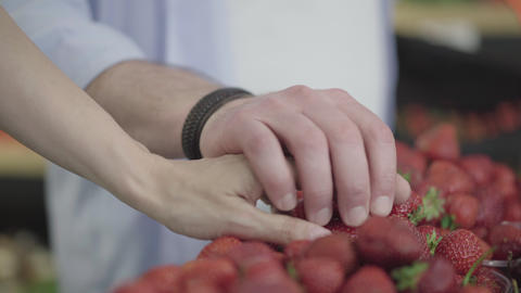 Male and female Caucasian hands touching each other as taking strawberry from Live Action