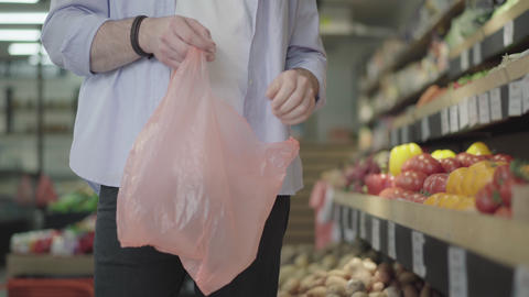 Male hands putting yellow tomatoes in plastic bag. Unrecognizable male buyer Live Action
