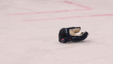 hockey player takes glove fallen on rink at sports game Live Action