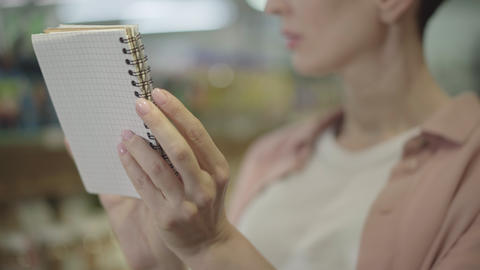 Close-up of female Caucasian hands holding notebook. Unrecognizable woman Live Action